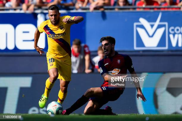 Jordi Alba of Barcelona and Nacho Vidal of Osasuna competes for the ball during the Liga match between CA Osasuna and FC Barcelona at on August 31...