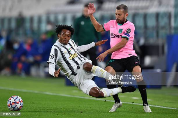 Jordi Alba of Barcelona is tackled by Juan Cuadrado of Juventus during the UEFA Champions League Group G stage match between Juventus and FC...