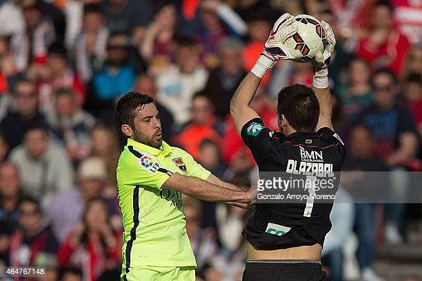 Jordi Alba of FC Barcelona clashes with goalkeeper Oier Olazabal of Granada CF during the La Liga match between Granada CF and FC Barcelona at Nuevo...