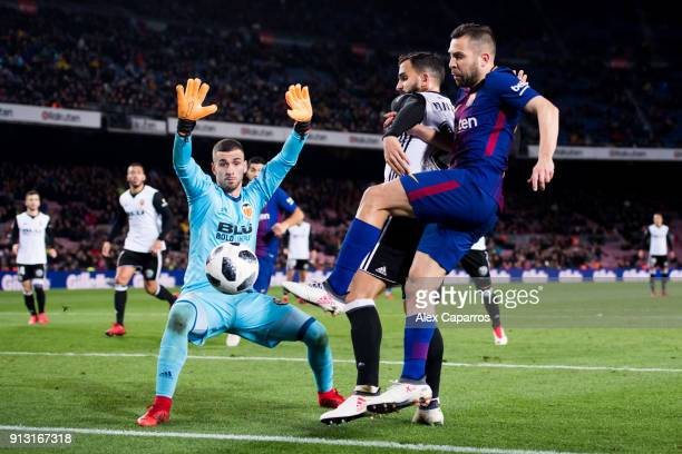 Jordi Alba of FC Barcelona fights for the ball with Martin Montoya and goalkeeper Jaume Domenech of Valencia CF during the Copa del Rey semifinal...