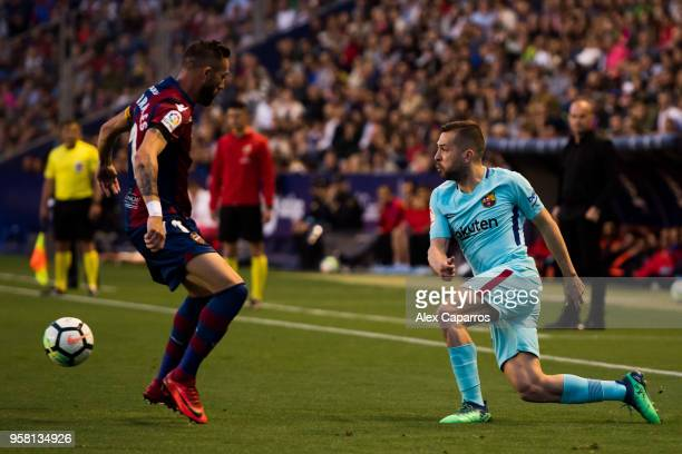 Jordi Alba of FC Barcelona plays the ball past Jose Luis Morales of Levante UD during the La Liga match between Levante UD and FC Barcelona at Estadi...