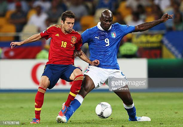 Jordi Alba of Spain and Mario Balotelli of Italy tussle for the ball during the UEFA EURO 2012 final match between Spain and Italy at the Olympic...