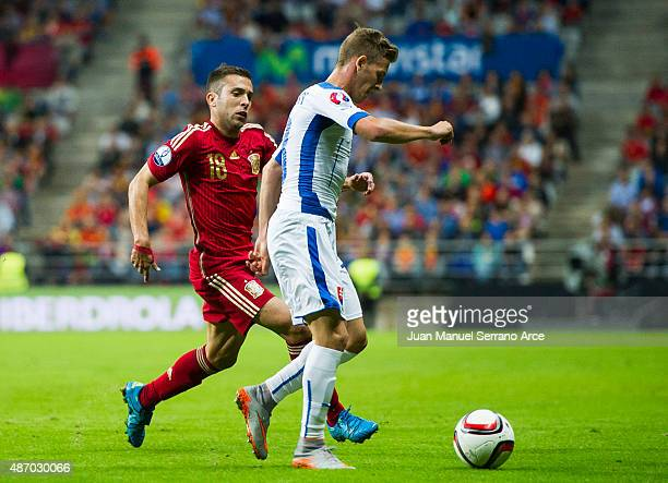Jordi Alba of Spain duels for the ball with Patrik Hrosovsky of Slovakia during the Spain v Slovakia EURO 2016 Qualifier at Carlos Tartiere on...