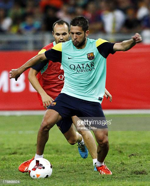 Jordi Allba of Barcelona FC runs with the ball and Andres Inesta chases during Barcelona FC training session at Bukit Jalil National Stadium on...