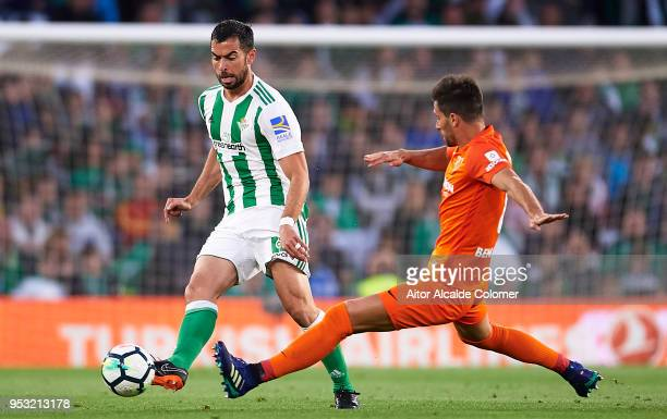 Jordi Amat of Real Betis Balompie being followed by Adrian Gonzalez of Malaga CF during the La Liga match between Real Betis and Malaga at Estadio...