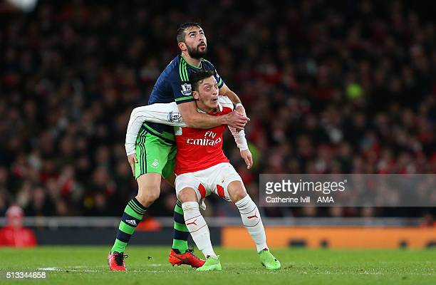 Jordi Amat of Swansea City holds back Mesut Ozil of Arsenal prior to Swansea City scoring a goal to make it 11 during the Barclays Premier League...