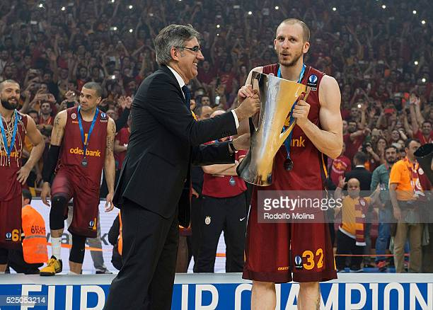 Jordi Bertomeu CEO and President of Euroleague Basetball gives the Champion's trophy to Sinan Guler #32 of Galatasaray Odeabank Istanbul at the end...
