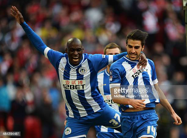 Jordi Gomez of Wigan Athletic celebrates with team-mate Marc-Antoine Fortune of Wigan Athletic after scoring a goal from the penalty spot during the...