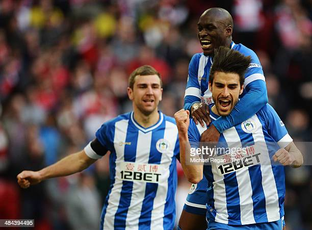 Jordi Gomez of Wigan Athletic celebrates with team-mates James McArthur and Marc-Antoine Fortune after scoring a goal from the penalty spot during...