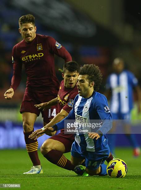 Jordi Gomez of Wigan Athletic is fouled by Sergio Aguero of Manchester City during the Barclays Premier League match between Wigan Athletic and...