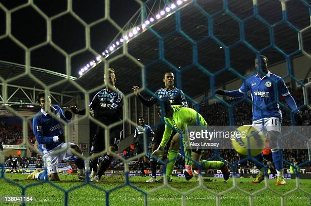 Jordi Gomez of Wigan Athletic scores an equalising goal past Petr Cech of Chelsea during the Barclays Premier League match between Wigan Athletic and...