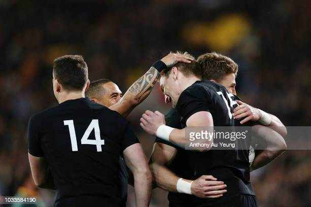 Jordie Barrett of the All Blacks celebrates with teammates Aaron Smith and Beauden Barrett after scoring a try during The Rugby Championship match...