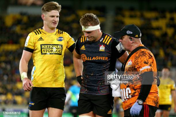 Jordie Barrett of the Hurricanes checks on Sam Cane of the Chiefs after he suffered a head knock during the round 9 Super Rugby Aotearoa match...