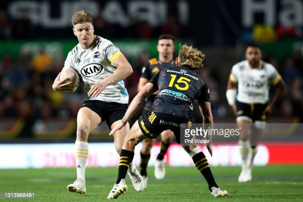Jordie Barrett of the Hurricanes is tackled by Damian McKenzie of the Chiefs during the round nine Super Rugby Aotearoa match between the Chiefs and...