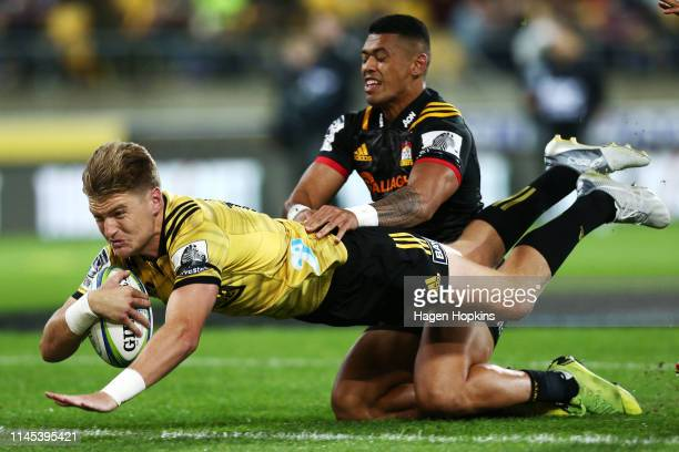 Jordie Barrett of the Hurricanes scores a try in the tackle of Etene NanaiSeturo of the Chiefs during the round 11 Super Rugby match between the...