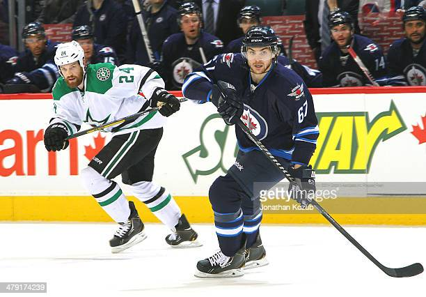 Jordie Benn of the Dallas Stars and Michael Frolik of the Winnipeg Jets follow the play up the ice during first period action at the MTS Centre on...