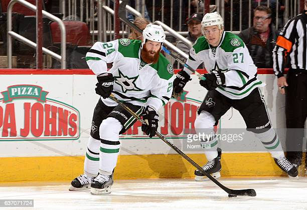Jordie Benn of the Dallas Stars passes the puck up ice while being supported by teammate Adam Cracknell against the Arizona Coyotes at Gila River...