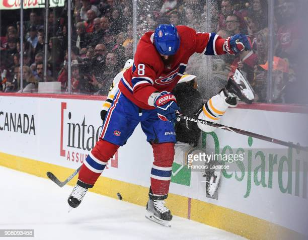 Jordie Benn of the Montreal Canadiens checks into the boards David Pastrnak of the Boston Bruins in the NHL game at the Bell Centre on January 20...