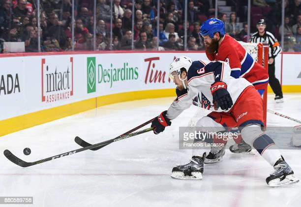 Jordie Benn of the Montreal Canadiens fights for the puck against Tyler Motte of the Columbus Blue Jackets in the NHL game at the Bell Centre on...