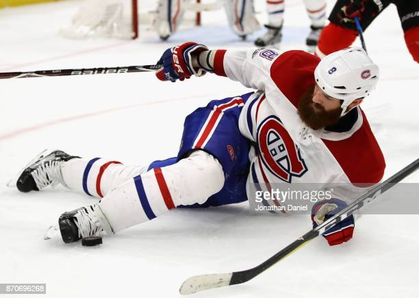 Jordie Benn of the Montreal Canadiens kicks the puck with his skate after falling to the ice against the Chicago Blackhawks at the United Center on...