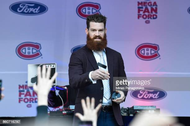 Jordie Benn of the Montreal Canadiens throws pucks towards the fans prior to the match against the Chicago Blackhawks during the NHL game at the Bell...