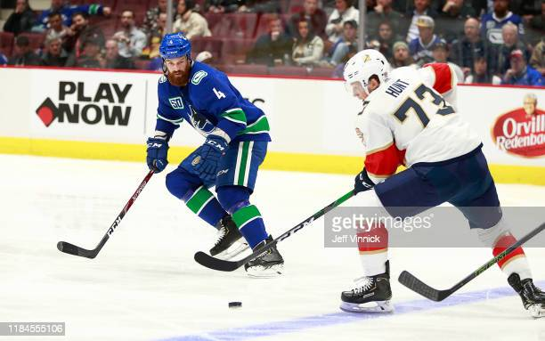 Jordie Benn of the Vancouver Canucks looks on as Dryden Hunt of the Florida Panthers skates up ice with the puck during their NHL game at Rogers...