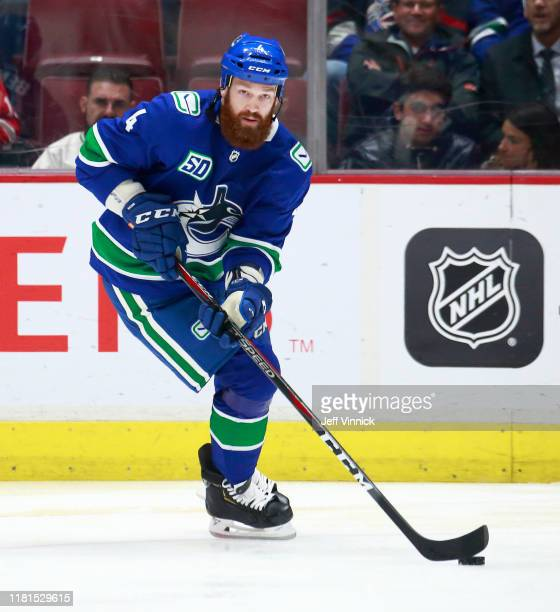 Jordie Benn of the Vancouver Canucks skates up ice with the puck during their NHL game against the Detroit Red Wings at Rogers Arena October 15 2019...