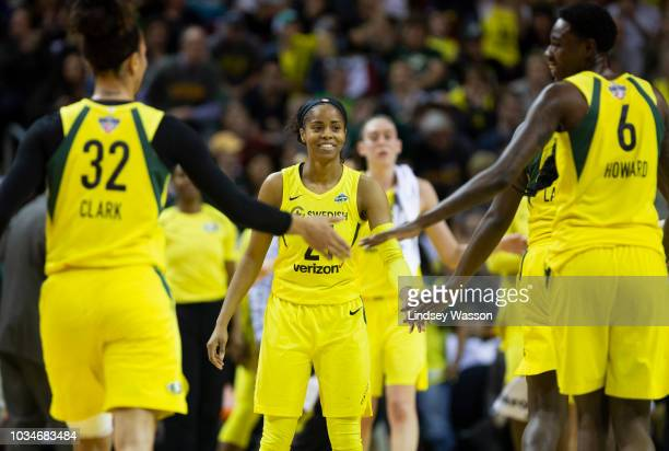 Jordin Canada of the Seattle Storm smiles as Alysha Clark and Natasha Howard greet each other during a timeout in the first half of Game 2 of the...