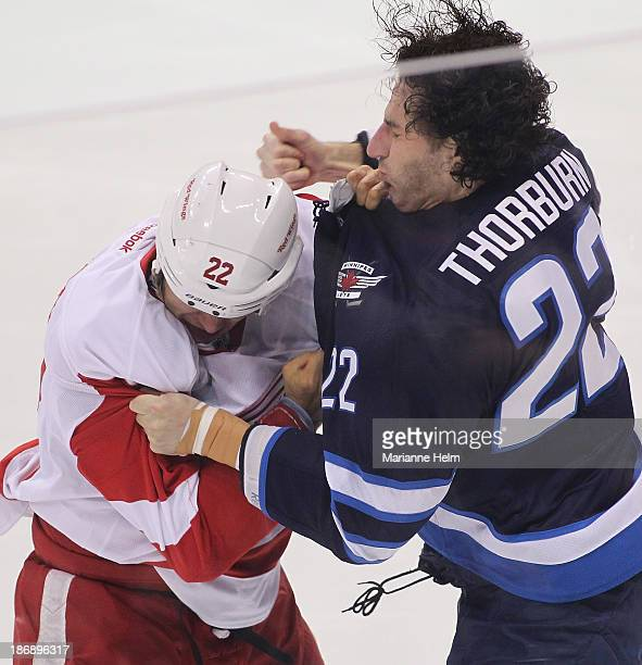 Jordin Tootoo of the Detroit Red Wings and Chris Thorburn of the Winnipeg Jets fights in the first seconds of the game in first period action in an...