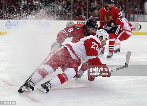Jordin Tootoo of the Detroit Red Wings hits the ice under pressure from Nick Leddy of the Chicago Blackhawks at the United Center on March 16 2014 in...