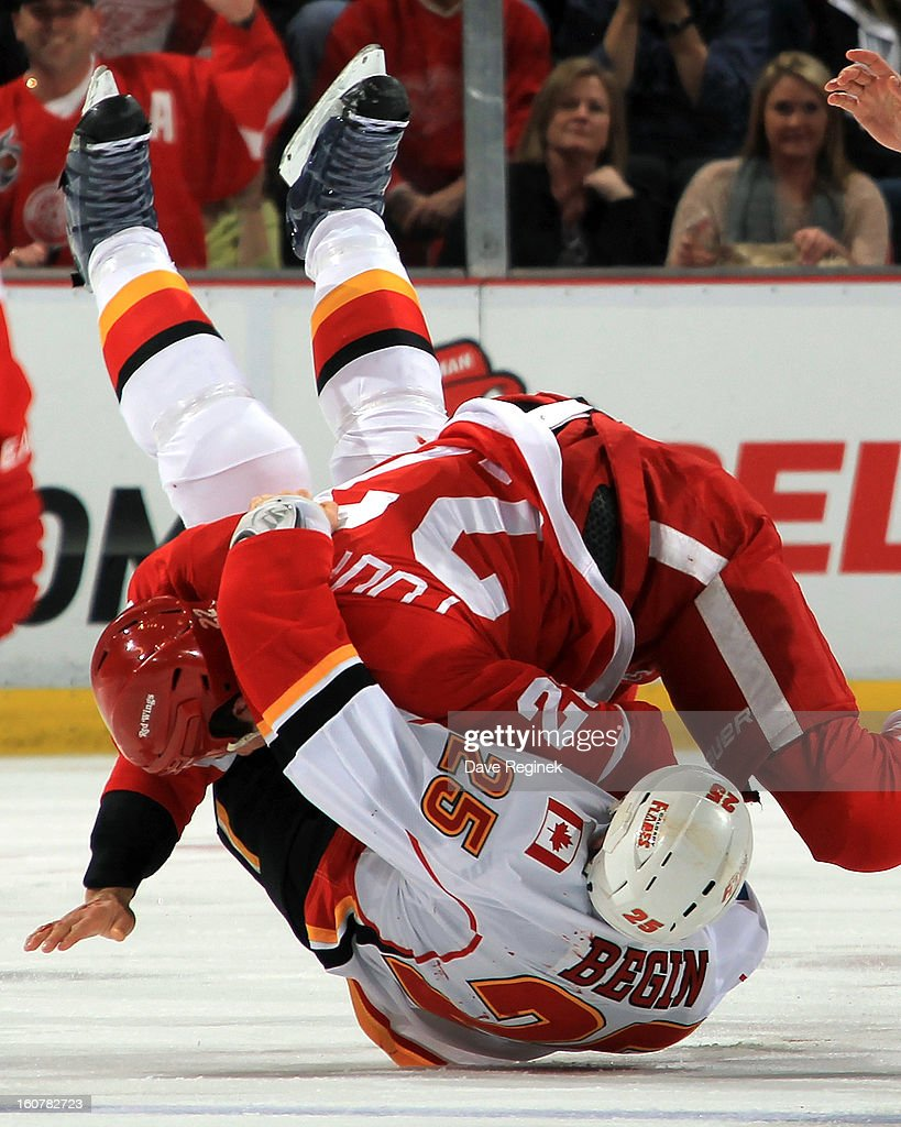 Jordin Tootoo #22 of the Detroit Red Wings slams Steve Begin #25 of the Calgary Flames to the ice during a NHL game at Joe Louis Arena on February 5, 2013 in Detroit, Michigan.