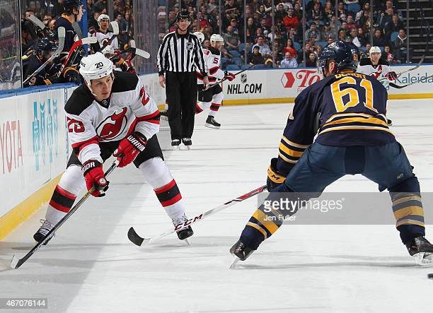 Jordin Tootoo of the New Jersey Devils passes the puck behind Andre Benoit of the Buffalo Sabres at First Niagara Center on March 20 2015 in Buffalo...