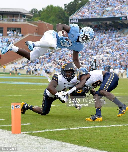 Jordon Brown of the North Carolina Tar Heels hurdles Derron Brown and Marloshawn Franklin Jr #18 of the California Golden Bears and into the end zone...
