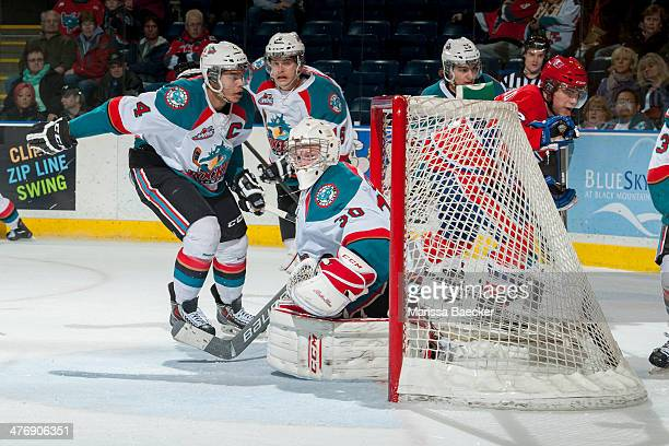 Jordon Cooke of the Kelowna Rockets defends the net as teammates Madison Bowey and Kris Schmidli skate against the Spokane Chiefs on March 5, 2014 at...