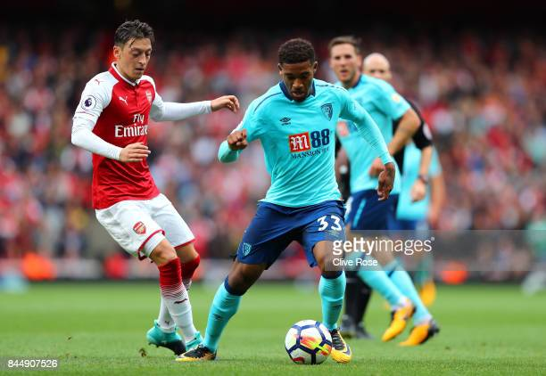Jordon Ibe of AFC Bournemouth and Mesut Ozil of Arsenal battle for possession during the Premier League match between Arsenal and AFC Bournemouth at...