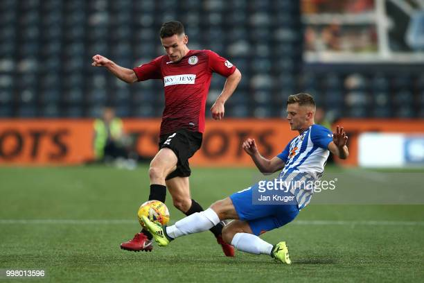 Jordon Jones of Kilmarnock FC slides in for a tackle on Paul McGinn of St Mirren during the Betfred Scottish League Cup match between Kilmarnock and...