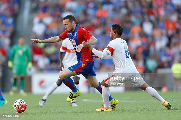 Jordon Mutch of Crystal Palace FC dribbles the ball past Kenney Walker of FC Cincinnati during the first half at Nippert Stadium on July 16 2016 in...