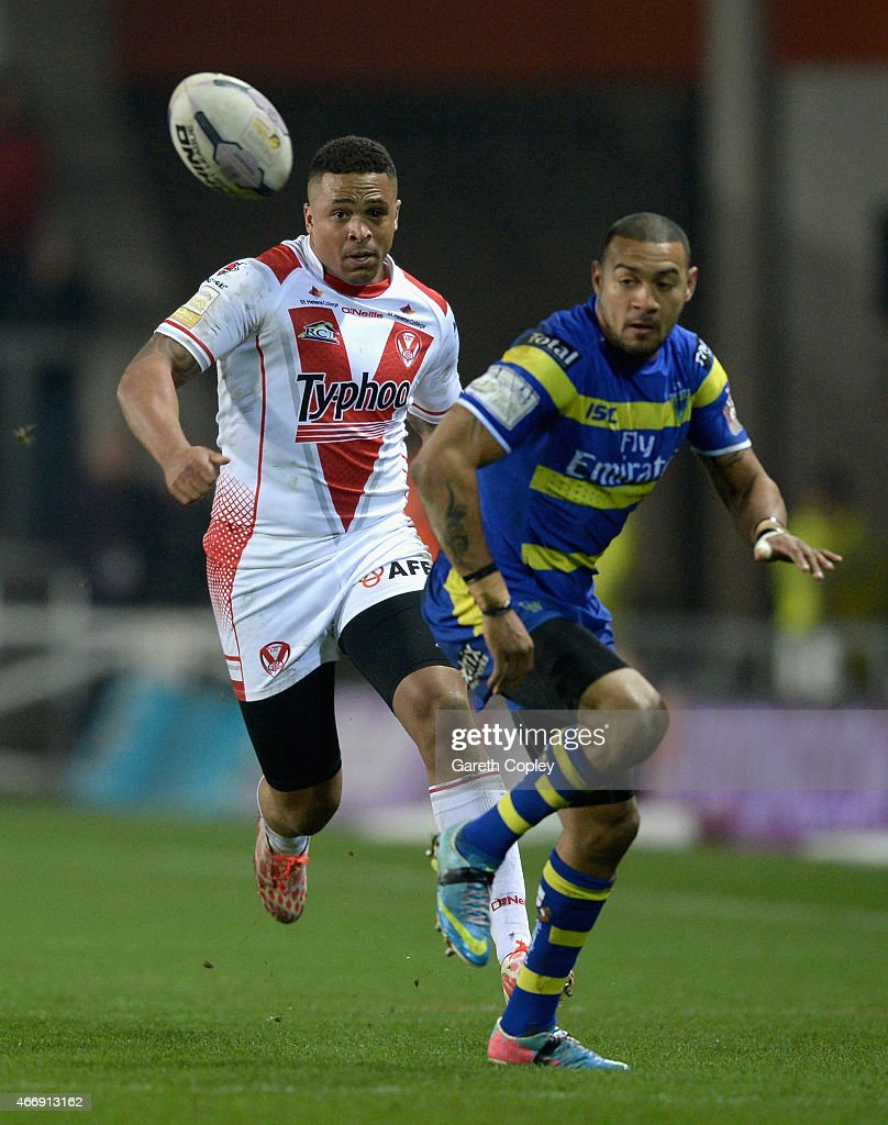 Jordon Turner of St Helens kicks past Kevin Penny of Warrington Wolves during the First Utility Super League match between St Helens and Warrington Wolves at Langtree Park on March 19, 2015 in St Helens, England.
