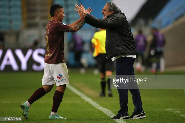 Jordy Alcivar of LDU Quito celebrates with his coach Pablo Marini after scoring the first goal of his team during a round of sixteen second leg match...