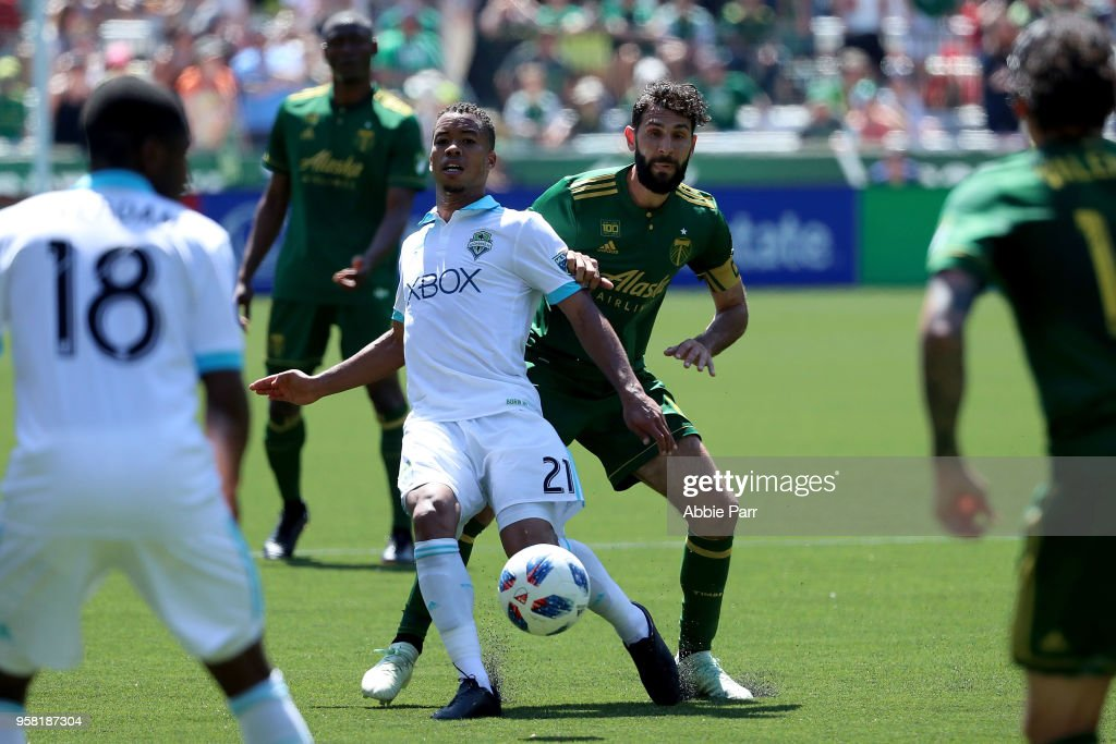 Jordy Delem #21 of the Seattle Sounders works against Diego Valeri #8 of the Portland Timbers in the second half during their game at Providence Park on May 13, 2018 in Portland, Oregon.