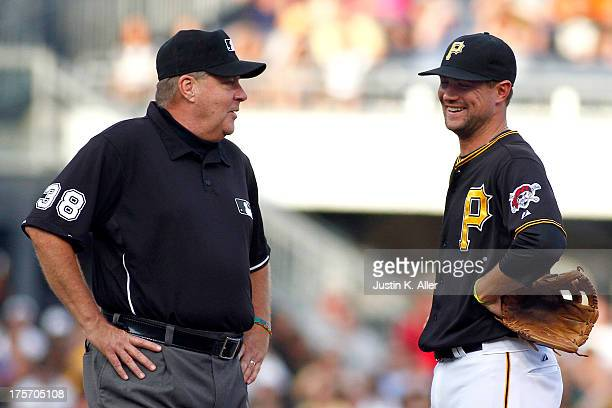 Jordy Mercer of the Pittsburgh Pirates and second base umpire Gary Cederstrom have a laugh after being struck by a ball in the first inning during...
