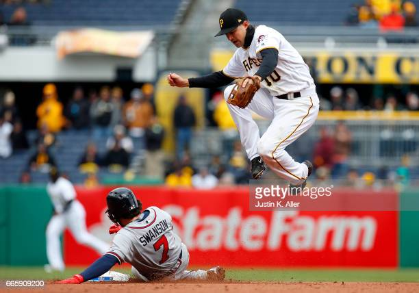 Jordy Mercer of the Pittsburgh Pirates records an out at second in the eighth inning against Dansby Swanson of the Atlanta Braves on Opening Day at...