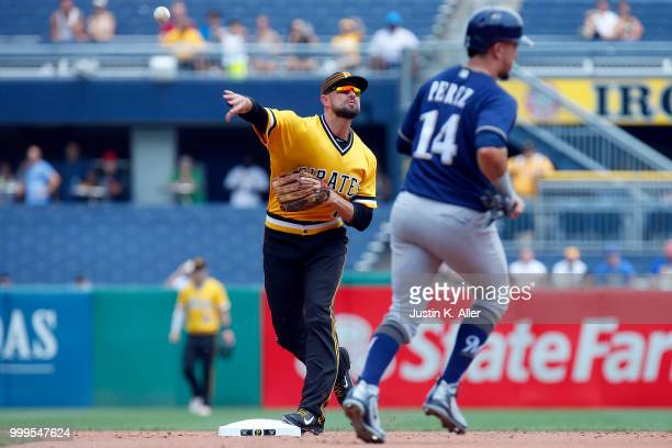 Jordy Mercer of the Pittsburgh Pirates turns a double play in the second inning against Hernan Perez of the Milwaukee Brewers at PNC Park on July 15...