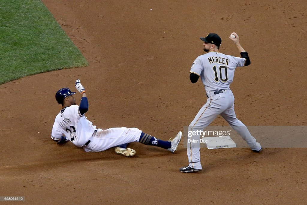Jordy Mercer #10 of the Pittsburgh Pirates turns a double play past Keon Broxton #23 of the Milwaukee Brewers in the fifth inning at Miller Park on June 19, 2017 in Milwaukee, Wisconsin.