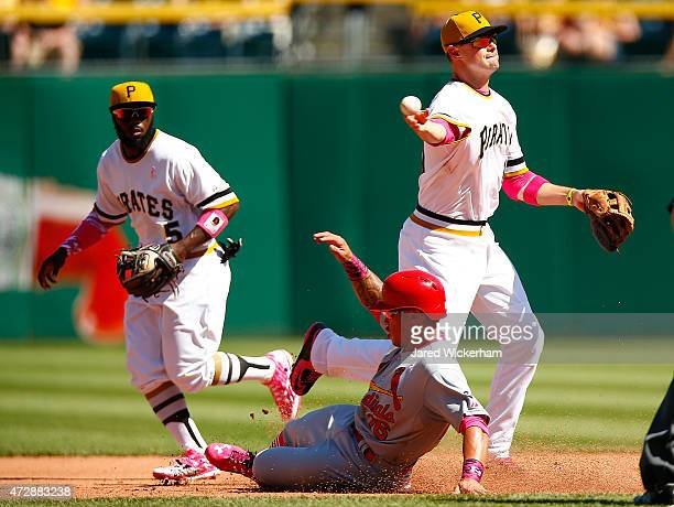 Jordy Mercer of the Pittsburgh Pirates turns the double play over Kolten Wong of the St Louis Cardinals in the eighth inning during the game at PNC...