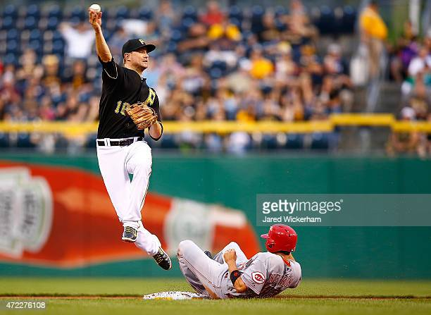 Jordy Mercer of the Pittsurgh Pirates turns the double play over Kristopher Negron of the Cincinnati Reds in the second inning during the game at PNC...