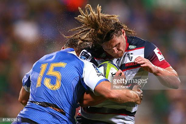 Jordy Reid of the Rebels gets tackled by Dane HallettPetty of the Force during the round one Super Rugby match between the Force and the Rebels at...