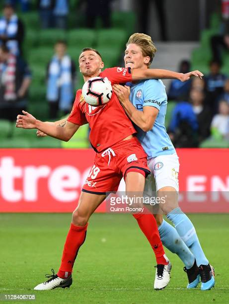 Jordy Thomassen of Adelaide United and Harrison Delbridge of the Melbourne City compete for the ball during the round 18 A-League match between...