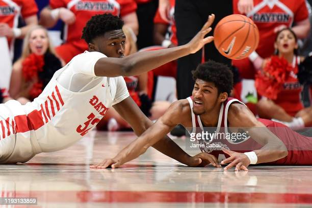 Jordy Tshimanga of the Dayton Flyers makes a pass after battling for control of the ball with Dibaji Walker of the Massachusetts Minutemen in the...