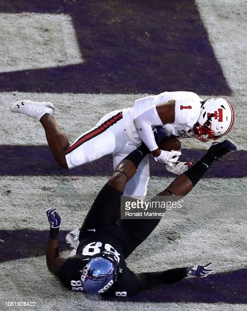 Jordyn Brooks of the Texas Tech Red Raiders makes a pass interception against Artayvious Lynn of the TCU Horned Frogs at Amon G Carter Stadium on...